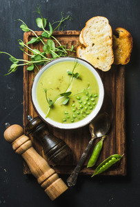Fresh homemade pea cream soup served with grilled bread