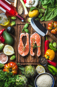 Dinner cooking ingredients  Raw uncooked salmon fish with vegetables  rice  herbs  lemon  spices and bottle of rose wine over rustic wooden board  top view