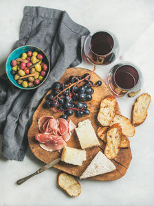 Red wine and snack set on board over grey background