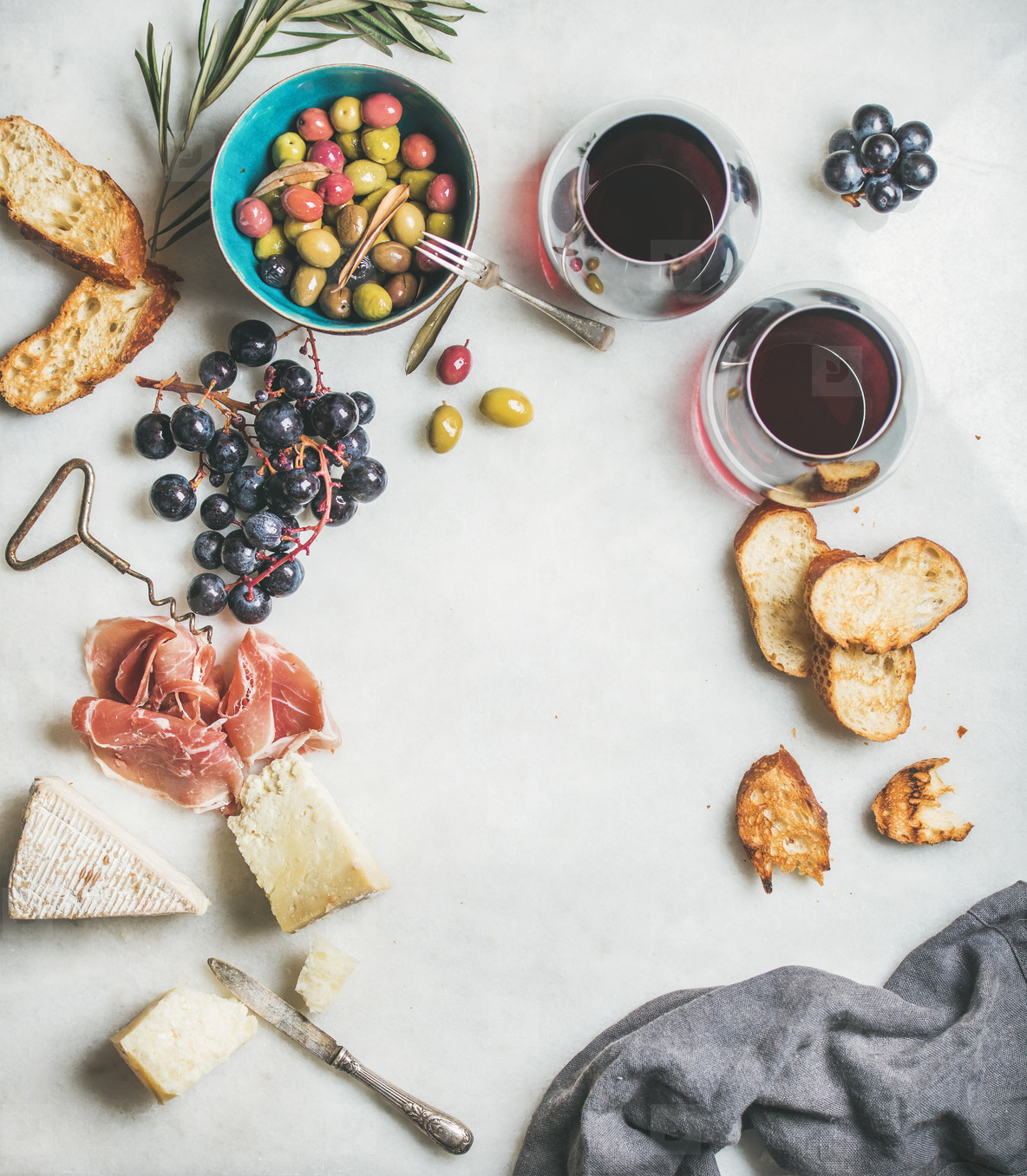 Cheese  olives  grapes  prosciutto  baguette and red wine  top view