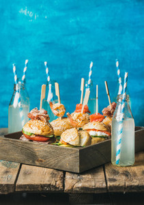 Different homemade burgers with sticks in wooden tray and lemonade