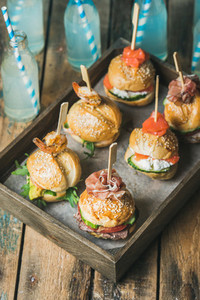 Homemade burgers in wooden tray over rustic table background
