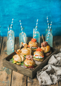 Homemade burgers in wooden tray and lemonade in bottles