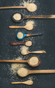 Quinoa seeds in different spoons over black stone background