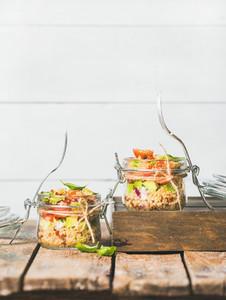 Homemade jar quinoa salad with cherry tomatoes  avocado and green basil