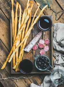Grissini bread sticks  sausage  black olives  wine in wooden tray