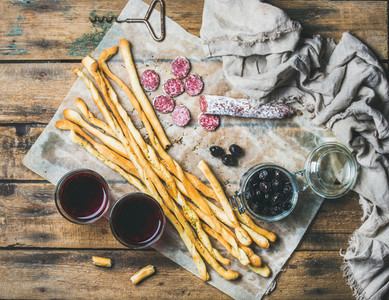 Grissini bread sticks  sausage  olives and red wine  wooden background