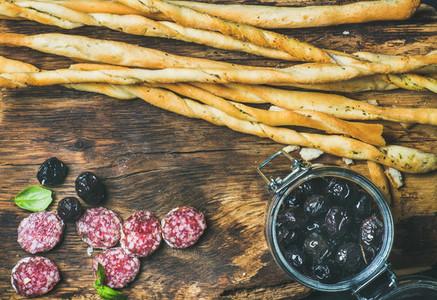Grissini bread sticks  sausage  black olives on wooden background