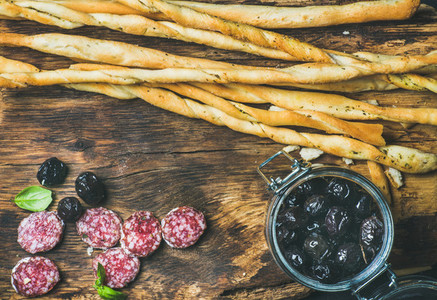 Grissini bread sticks sausage black olives on wooden background