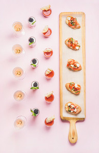 Various snacks brushetta sandwiches gazpacho shots desserts over pink background