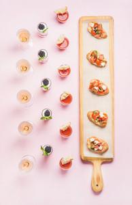 Various snacks brushetta sandwiches gazpacho shots desserts over pink background