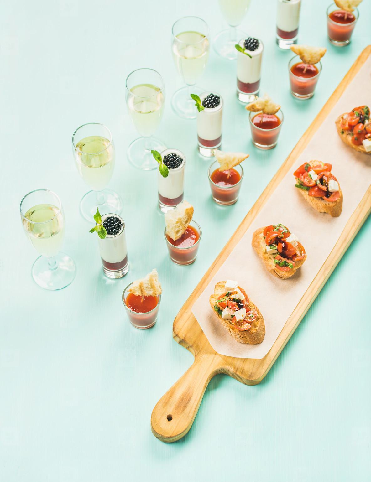 Snacks  brushettas  gazpacho shots  desserts  champagne over pastel blue background