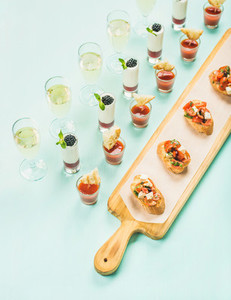 Snacks brushettas gazpacho shots desserts champagne over pastel blue background