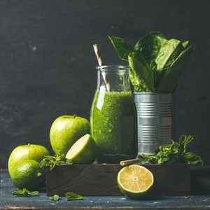 Green smoothie with apple romaine lettuce lime mint Dark background