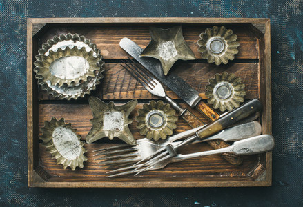 Old vintage tin baking molds and cutlery in wooden tray