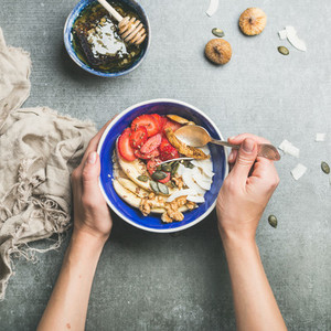 Eating healthy breakfast bowl over grey concrete background