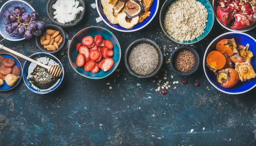 Ingredients for healthy breakfast over dark blue background  copy space