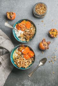 Oatmeal quinoa granola yogurt seeds honey persimmon in blue bowls