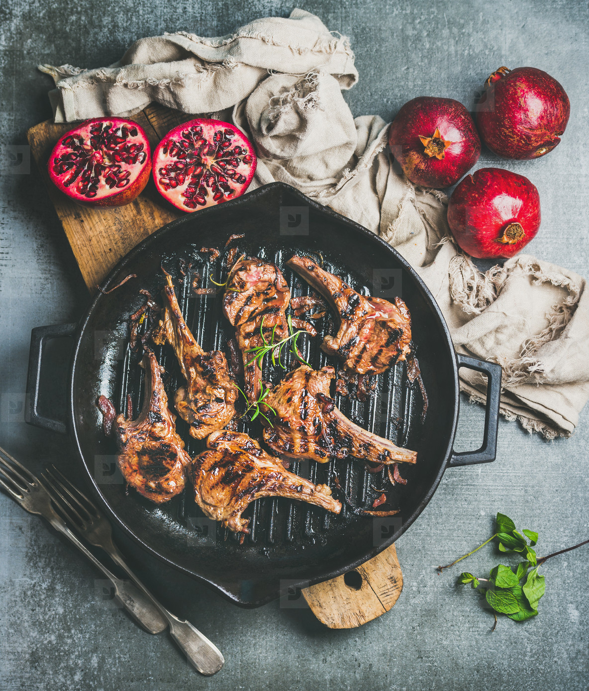Grilled lamb meat chops served with fresh pomegranates  grey background