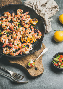 Seafood dinner with grilled tiger prawns in pan grey background