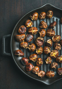 Roasted chestnuts in grilling pan over dark wooden background
