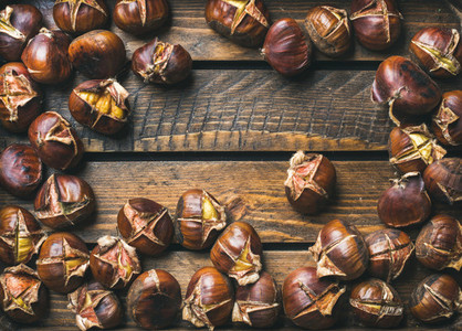 Close up of roasted chestnuts over rustic wooden background