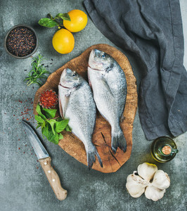 Uncooked sea bream fish with lemon  herbs  spices  olive oil