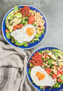 Healthy breakfast bowls with fried egg  chickpea sprouts  seeds  greens