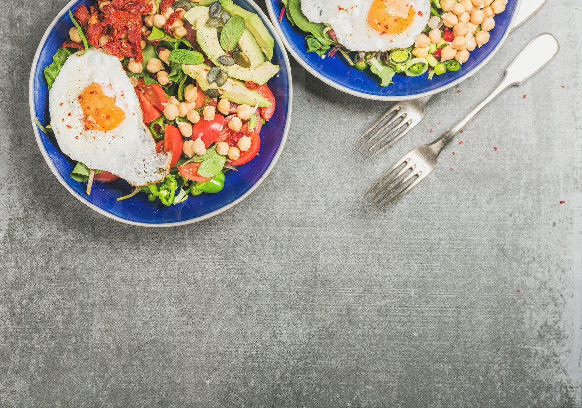 Healthy breakfast in blue ceramic bowls over grey background