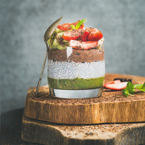 Healthy raw breakfast concept in glass over wooden board