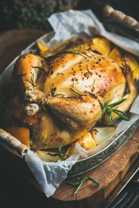 Close up of Christmas roasted whole chicken with rosemary bulgur oranges