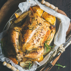 Close up of roasted chicken with oganges bulgur and rosemary