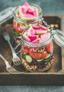 Close up of healthy vegetarian salad in jars in wooden tray
