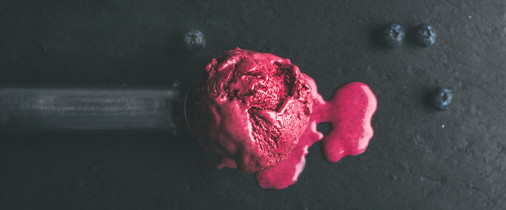 Melting scoop of blueberry ice cream over black slate stone background