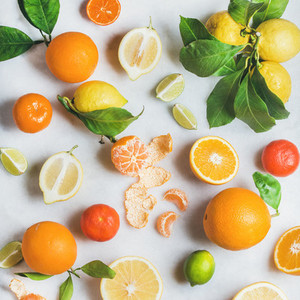 Variety of fresh citrus fruit over light grey marble background