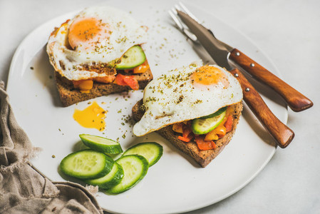 Breakfast toasts with fresh vegetables and fried egg on plate