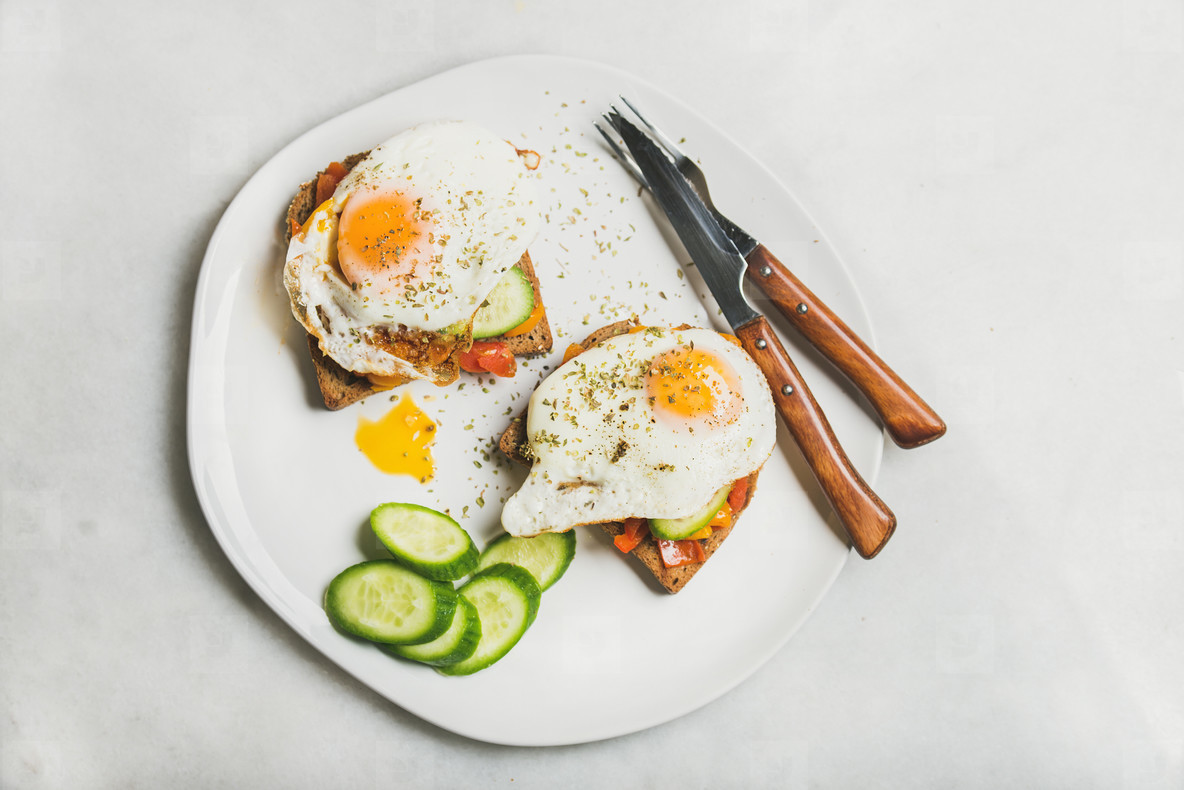 Breakfast toast with fried eggs and vegetables  top view
