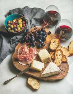 Wine and snack set on wooden board over grey background
