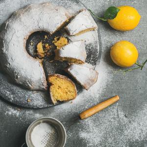 Homemade gluten free lemon bundt cake over grey concrete background