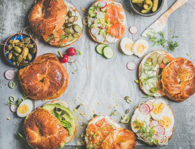 Variety of fresh bagels with different fillings copy space