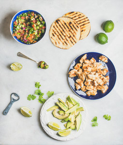 Ingredients for cooking chicken and avocado tacos  grey marble background