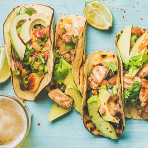 Healthy corn tortillas and beer over blue background  square crop