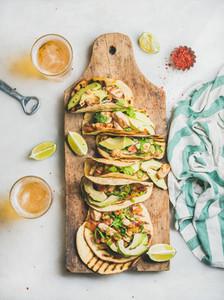 Corn chicken and avocado tortillas on wooden board  top view
