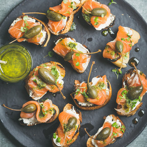 Homemade salmon crostini with cream cheese watercress capers and pesto suace