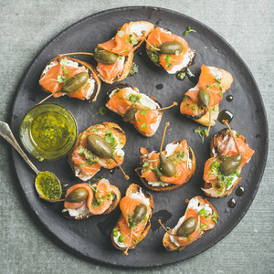 Homemade salmon crostini in black plate over grey background