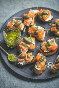 Homemade Italian salmon crostini in black plate over grey background