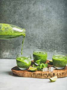 Fresh smoothie with ice  mint and lime pouring from bottle