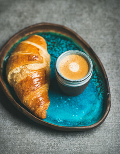 Cup of espresso coffee and croissant in blue ceramic tray