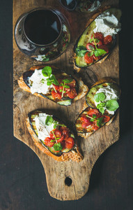 Glass of red wine  brushetta with vegetables  cream cheese  arugula