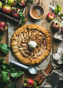 Homemade apple crostata with cinnamon ice cream scoop and fresh apples